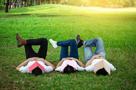 一生懸命勉強するので、人々のグループは顔に本を持って眠ります