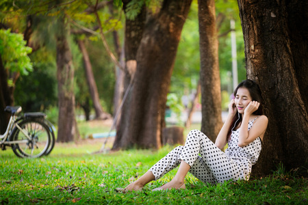 Asian girl sitting relax against tree, listen music with earplug in park with bicycle near Reklamní fotografie
