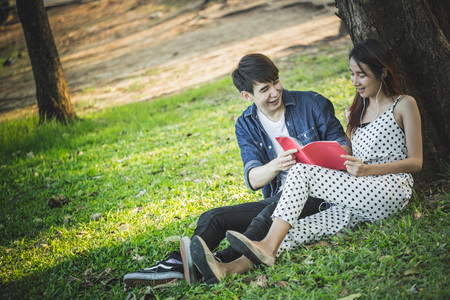 Couple of high students read a book and listen music under a tree in park