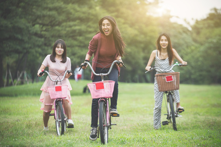 group of girls ride a bicycle in park, having fun by play together Reklamní fotografie