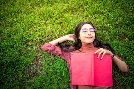 Portrait of high school girl lay down and read a book in park, education concept