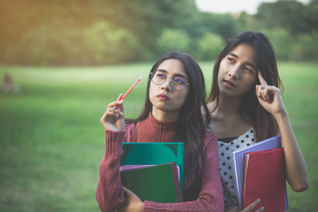 two girls thinking in park and hold the books, create knowledge concept
