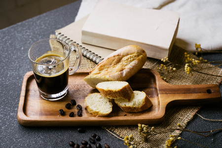 A coffee, bread, wood plate and book setting on black background