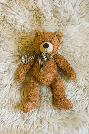 lies down: Brown teddy bear with ribbon lies down on the carpet.