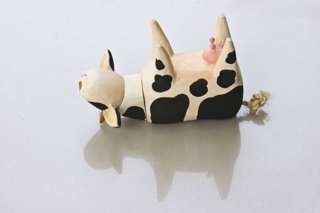 overturned: An overturned wooden cow toy on white background. Stock Photo