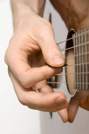 virtuoso: Right hand of guitar player using a plectrum Stock Photo