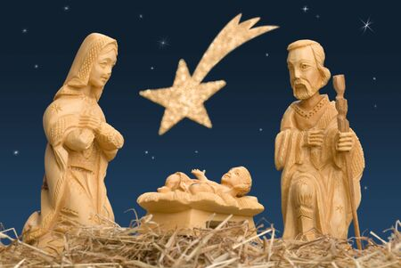 Wooden figures of Mary and Joseph watching baby Jesus, with night sky and comet Stock Photo
