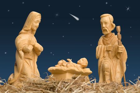 Wooden figures of Mary and Joseph watching baby Jesus, with night sky and comet photo