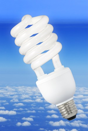 Low-energy light bulb over a blue sky background above the clouds photo