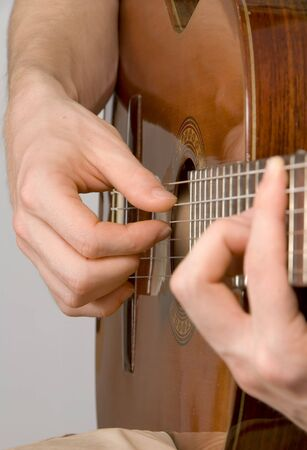 virtuoso: Hands of male guitarist playing a classical guitar