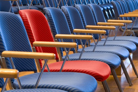 Single red seat in a row of blue seats photo