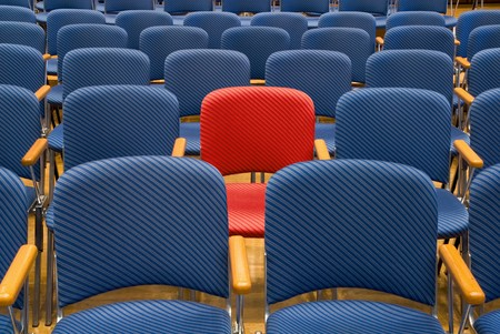 centred: Single red seat in the middle of rows of blue seats