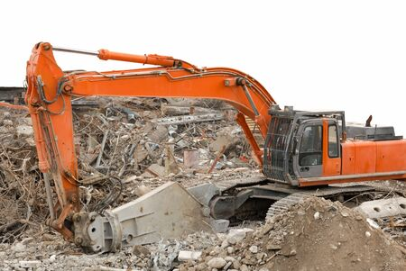 Partly isolated orange hydraulic shovel in the middle of demolished scrap. photo