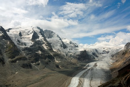 Austrian mountain range and glacier with fluffy white clouds photo