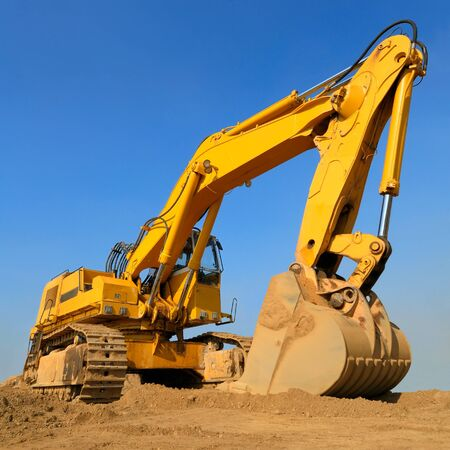excavator: Heavy earth mover on a sunny day with the blue sky in the background