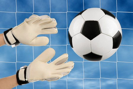 Soccer goalkeeper�s hands reaching for the ball, with net and sky in the background photo