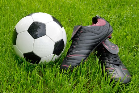 Closeup of a shiny soccer ball and black soccer shoes on fresh grass Stock Photo - 7055073