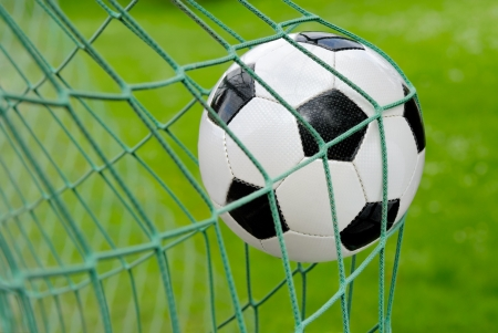 aiming: Close-up of a soccer ball flying into the net