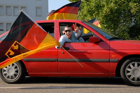 football party: A German soccer fan showing the victory sign and swinging his large flag in a red car during a motorcade