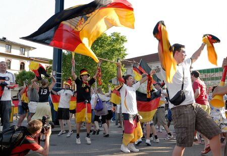to sway: German soccer fans dancing and waving their flags on the street during the world championship 2010