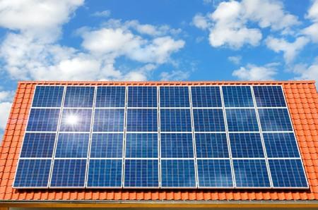 Dach mit Solar-Panel reflektieren der Sonne, im Hintergrund einen perfekten Himmel mit flauschige Weiße Wolken