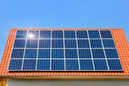 cobradores: Techo con paneles solares que refleja el sol, en el fondo un perfectamente despejado cielo azul