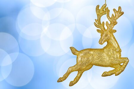Blue Christmas background with glittering golden deer in front of defocussed lights photo