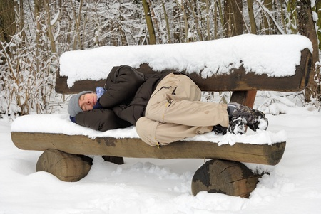 Exhausted young man sleeping on a snow-covered bench, ignoring the chill photo