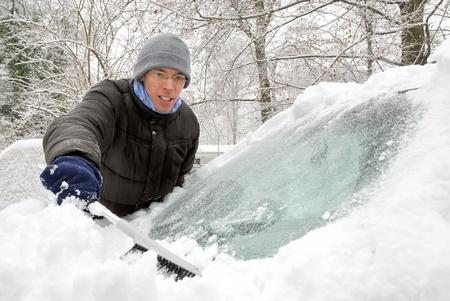 deep freeze: Joven cepillado de la nieve en el parabrisas de su coche