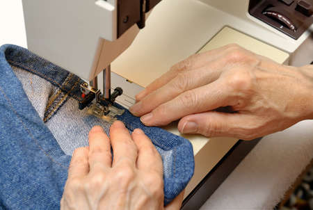 Experienced female hands working on a sewing machine photo
