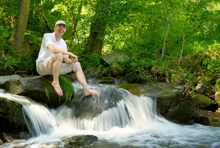 forest stream: Happy young man sitting at a beautiful creek and cooling his foot in the water Stock Photo