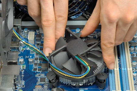 Studio close-up of a technicians hands installing a fan on the motherboard