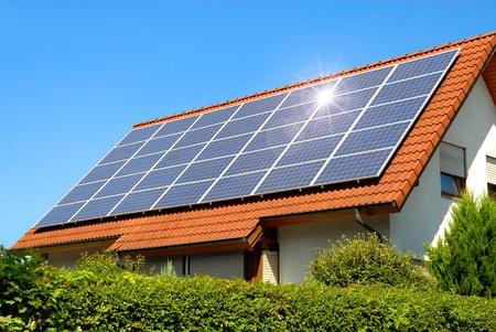 cobradores: Panel solar en un techo rojo que refleja el sol y el cielo azul despejado Foto de archivo