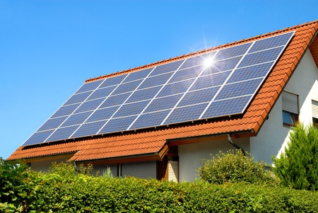 Solar panel on a red roof reflecting the sun and the cloudless blue sky photo