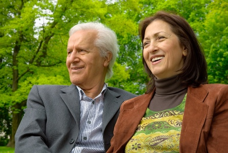 enjoy life: Happy active senior couple sitting in a park and having a nice time