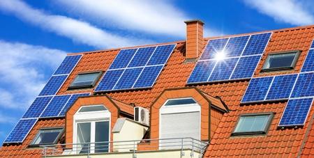 energia solar: Panel solar en un techo rojo con las nubes blancas y el reflejo del sol
