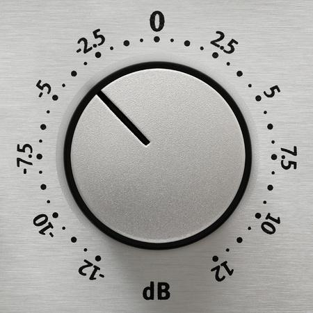 Studio close-up van een metalen volumeknop met getallen van -12 tot 12 dB