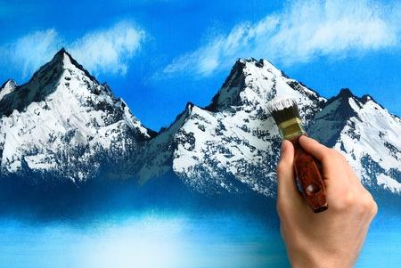 Een kunstenaar hand houden een borstel en een berglandschap op een doek schilderij