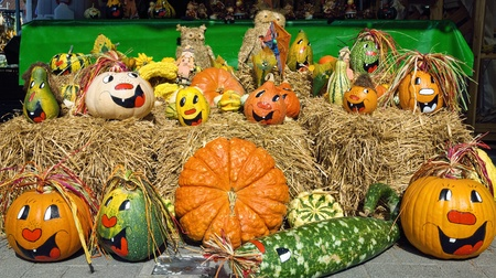 Cheerful looking painted pumpkins on straw, nicely arranged for sale photo