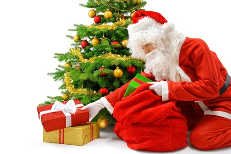Nice Santa putting gift boxes under the Christmas tree, studio isolated  Stock Photo