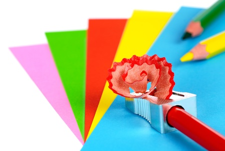 Colorful sheets of paper and color pencils being sharpened photo
