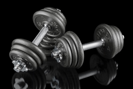 Low-key studio shot of two heavy dumbbells on black with reflections  photo