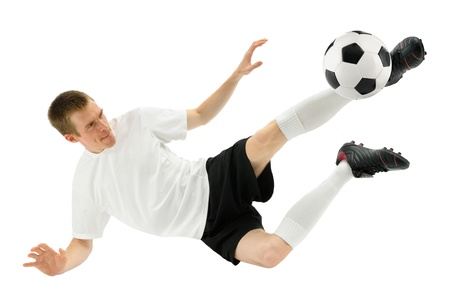 midair: Isolated studio shot of a soccer player kicking the ball in mid-air
