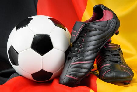 Shiny soccer shoes and ball nicely arranged on the German flag Stock Photo - 13535624