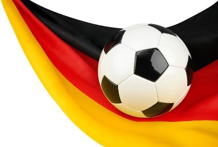 campeonato de futbol: Balón de fútbol en una bandera alemana que cuelga de un modo fantástico como un símbolo de amor de Alemania de fútbol