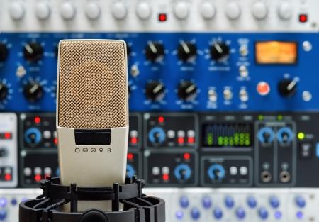 equipo de sonido: Micrófono de estudio profesional y un rack de equipos de audio, con foco superficial