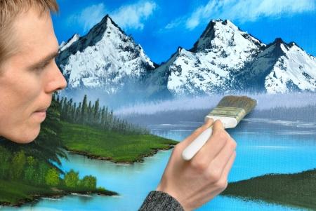 hand schilderen: Man kunstenaar die werkt met geconcentreerde uitdrukking op een mooie blauwe landschap schilderij Stockfoto