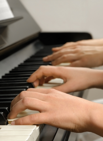 piano player: Four hands playing on the piano keys while the teacher gives the student a lesson