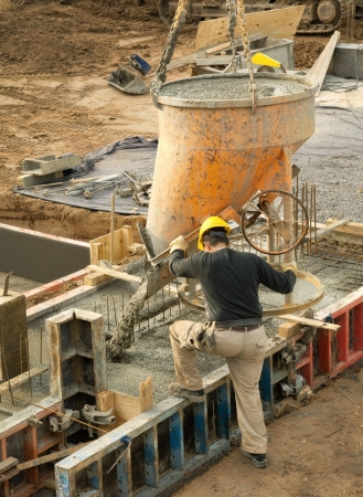 Construction worker in action  concrete being poured into the foundation Stock Photo - 14529432