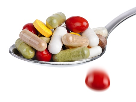 Medical concept  spoon piled with colorful pills, with one tablet falling down, isolated on white photo